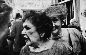 Hedda Hopper eavesdropping on Louella Parsons.