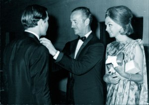 Hjordis looks on as David Niven fixes son Jamie's tie at the premiere of 'The Pink Panther', with JAmie