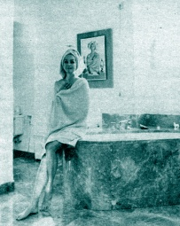"""Hjördis Niven on the edge of the brown marble bathtub. There there are large built-in cabinets with space for underwear, trousers and jumpers so that she can get fully dressed after a bath without having to go leave the bathroom."""